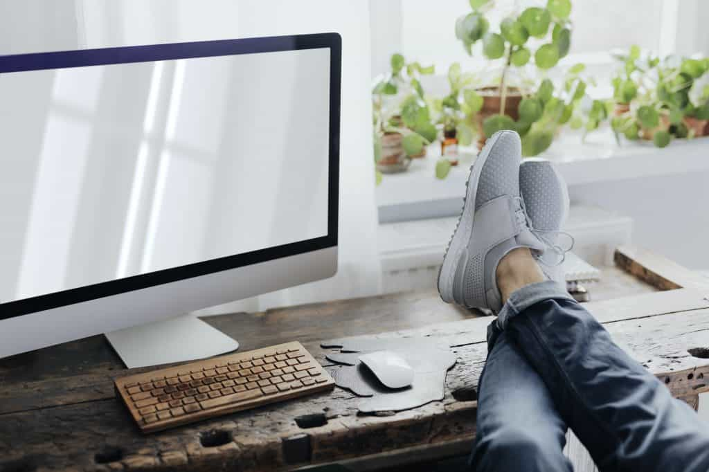 Lazy man putting his feet up on the workstation